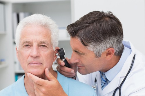 A doctor using a special equipment to assess the condition and severity of otorrhea in an elderly patient.image